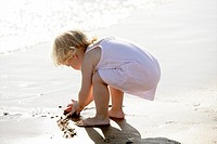 Beautiful little girl playing on the beach sand