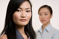 An attractive asian businesswoman with a colleague standing behind out of focus