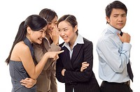 Three asian businesswomen gossip about their boss behind his back