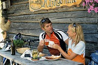 young mountain biker couple eating at an alpine hut