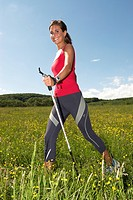 young woman nordic walking on grassland