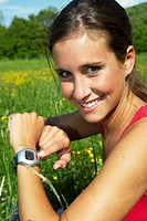young beautiful woman with pulse watch, jogging in a flower meadow