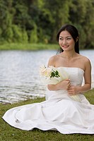 A beautiful asian woman in a wedding dress poses by the side of a lake, holding yellow roses