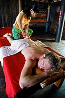 A TOURIST enjoys a THAI MASSAGE at a beach resort, Thailand, Bangkok