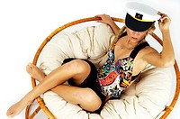 Young woman wearing swimsuit and seaman's cap, lying in a lounge chair