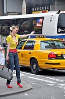 blond woman hailing a taxi at Time Square, USA, New York City, Manhattan