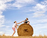 girl helping woman to climb hay bale