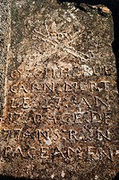 Old gravestone carved in French writing and a skull and crossbones