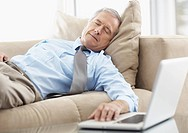 Tired businessman napping on a couch