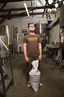 Portrait of young man working in a brewery, day dreaming