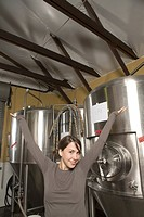 Smiling female worker in brewery with arms outstretched