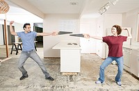 Playful couple dueling with saws in kitchen