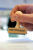 hand with a stamp Haftpflicht, liability