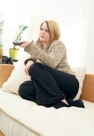 blond young woman with remote control on couch