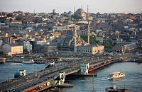 View across the Eminoenue district with the Galata Bridge spanning the Golden Horn and the New Mosque in front of Nuru Osmaniye Mosque, Istanbul, Turk...