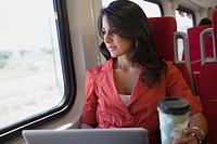 Hispanic woman using laptop on train