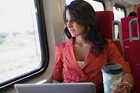 Hispanic woman using laptop on train