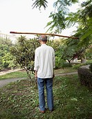 Chinese man balancing stick on head