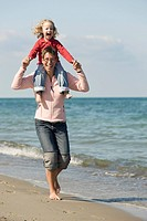 A mother carrying her daughter on her shoulders on the beach