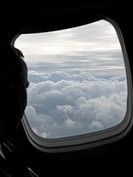 Man is watching out of the window of an airplane on a cloudy sky
