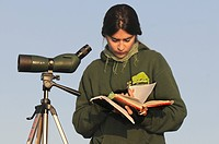 cute young female ornithologist with spotting scope and bird book, Greece, Peloponnes