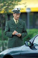 police man writing a parking ticket at traffic control, Germany