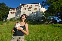 Young woman carrying a Pygmy Rabbit (Brachylagus idahoensis) in front of Schloss Friedberg castle, Volders, Tyrol, Austria, Europe