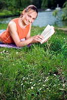 woman lies on meadow in a park reading a book