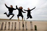 three young women jumping from wooden piles of groyne at the beach, Netherlands, Zeeland, Breskens, Sluis