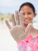 Hispanic girl displaying sand_covered hand