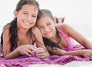 Hispanic sisters relaxing on towel at beach