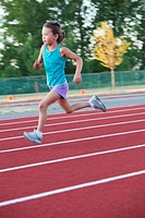 Mixed race girl running on track