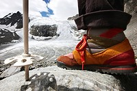 Foot and ski stock of a hiker hiking from Peiljoch alongside the Sulzen Glacier, Stubai Valley, Tyrol, Austria, Europe