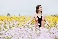 Hispanic woman standing in field of flowers