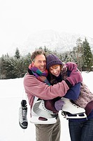 Italy, South Tyrol, Seiseralm, Couple carrying ice skates, embracing, smiling, portrait