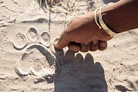 Africa, Botswana, Okavango Delta, man pointing on animal foot print