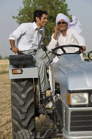Farmer talking on a mobile phone while driving a tractor with his son