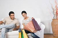 Couple sitting on a couch with shopping bags