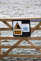 Beware of the bull sign on gate with field covered with hoar frost in Wiltshire in January