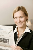 Smiling blonde woman reading a newspaper