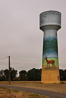 A water tower in Northern France painted with fields, trees and deer