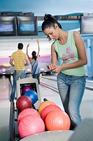 Young woman looking at her wrist with her friends playing in the background in a bowling alley