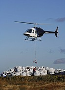 Helicopter ferrying seed laden compost to workers regenerating moorland near Torside Reservoir