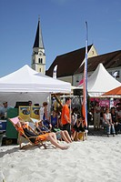 Kids sitting on deck chairs, spectators at a beach volleyball tournament on the main square of Muehldorf am Inn, Upper Bavaria, Bavaria, Germany, Euro...