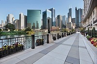 Sidewalk along Chicago River with skyline beyond
