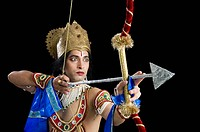 Stage artist dressed_up as Rama and holding a bow and arrow