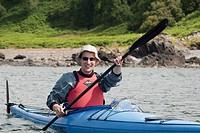 Sea kayaker paddling around the small islands along the coast of Oban, Argyll, Scotland