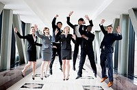 Business people jumping with hands outstretched and smiling together