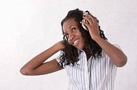Young woman looking up with smile and listening music with headset
