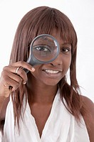 Young woman putting magnifying glass on one eye and smiling